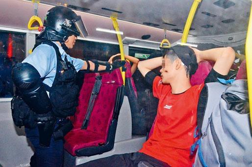 防暴警登上巴士搜查,乘客雙手抱頭接受警員查問。