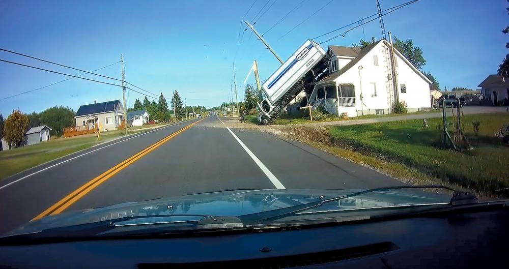 汽車視頻攝得大貨櫃車失控,尾部車貨櫃擱在一民宅屋頂,司機落車察看。 CBC