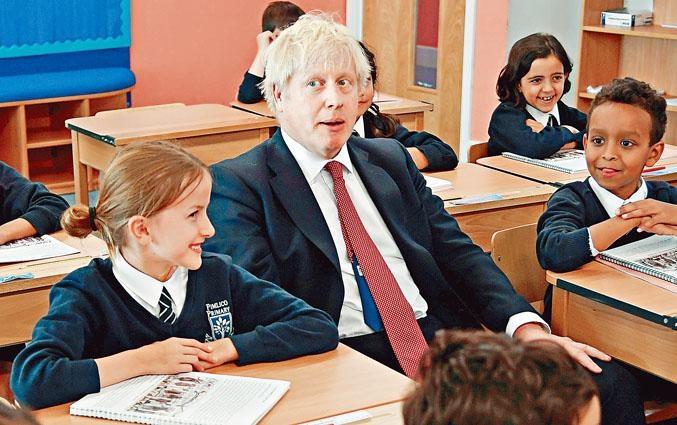 英國國會踏入休會期,首相約翰遜周二到訪倫敦一所小學。