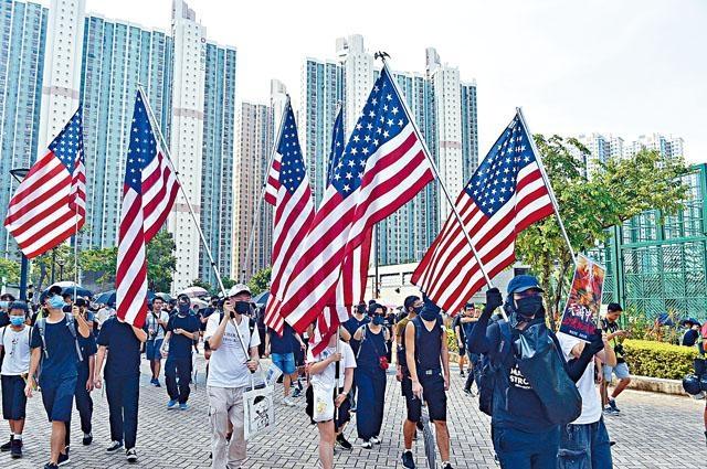 ■部分示威者遊行時舉起美國旗。