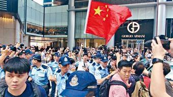 其中一名揮舞國旗人士情緒高漲,警員築起人鏈護送。