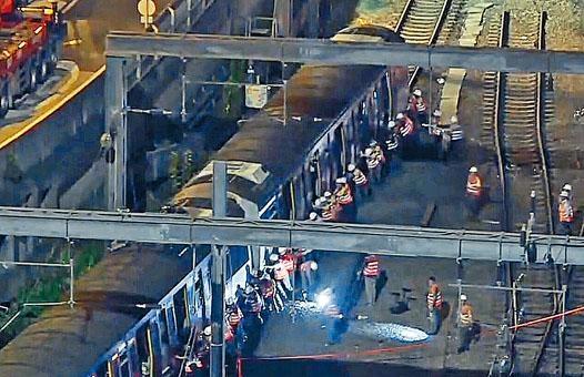 工程人員合力將列車推回月台。