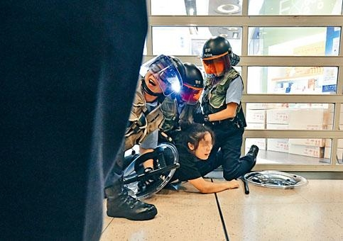 一名女子被防暴警按在地上拘捕。