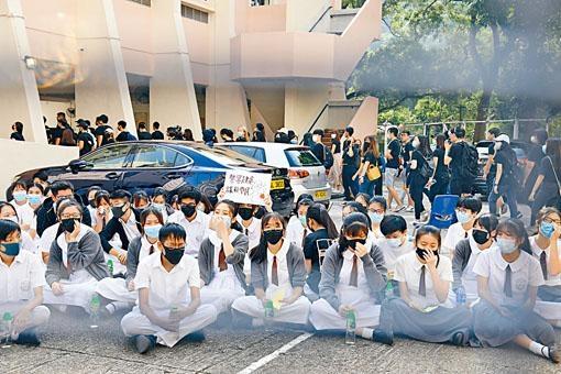 何傳耀紀念中學一群學生戴上口罩靜坐。