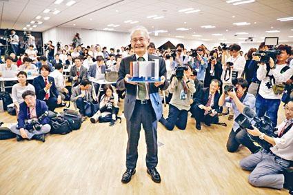 吉野彰在記者會上展示鋰離子電池模型。