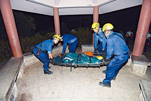 消防員將死者遺體抬落山。
