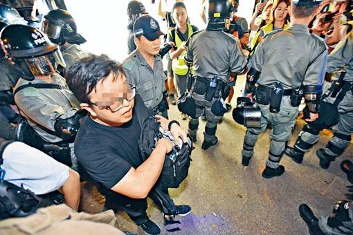 防暴警在一名懷疑教職員的袋中發現一把鎅刀,將他帶返警署了解。
