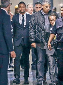 古巴高汀被鎖上手扣押到法院,為非禮案受審。