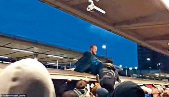 在倫敦景寧鎮站爬上地鐵車頂的示威者,被人抓住腳拉下來。