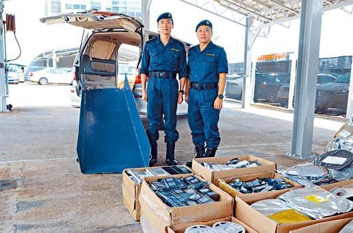 海關海域調查組指揮官梁耀文(右),展示緝獲走私物品並講述案情。