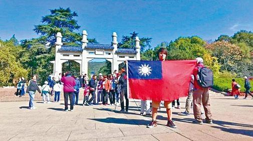 ■楊翰傑在中山陵前手舉青天白日旗拍照留念。
