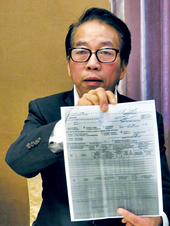 鄭煜深昨展示法庭撤銷其控罪文案的影印本。