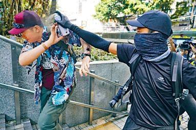 ■黑衣人在尖沙嘴警署外向撐警內地男子噴漆。