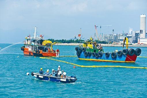 在海上污染事故演習中,油污清理隊伍架設圍欄及海上屏障防止油污擴散。