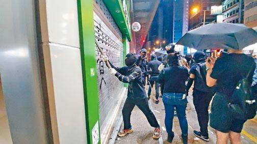 ■示威者向店鋪閘門進行破壞。