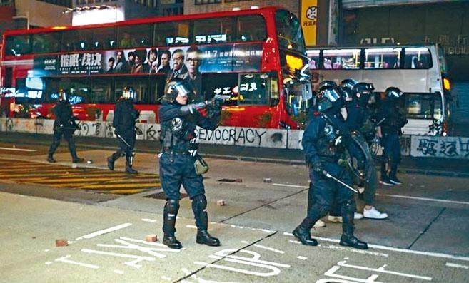 ■穿上保護裝備的探員遭示威者狂掟石,為自保向天鳴槍示警。