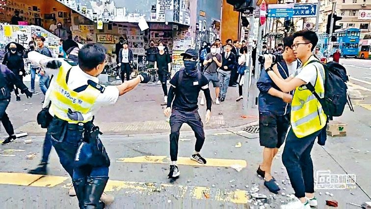 警署警長左手箍住一名白衣人,右手拔出佩槍指向黑衣人。