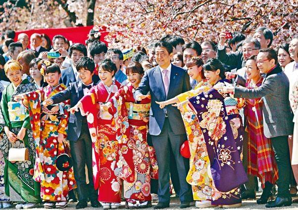 今年四月,安倍晉三(中)與受邀民眾在賞櫻會留影。