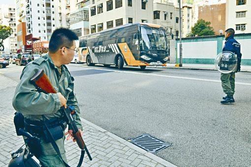 眾被告由旅遊巴載抵法庭,警員荷槍戒備。
