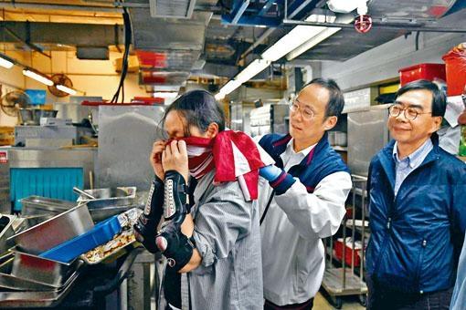 ■衛炳江(中)在廚房了解現況時,細心為留守者綁實美國旗口罩。